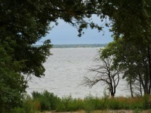 Lake Texoma framed by trees and plants seen from a roadend in Preston Bend, Texas